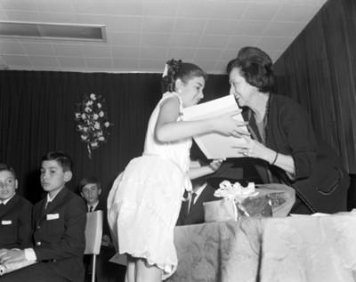 Mujer felicita y entrega documento a una estudiante en un estrado durante festival de clausura