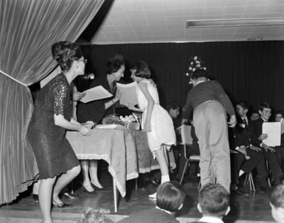 Mujer entrega documento a una estudiante en estrado durante festival de clausura