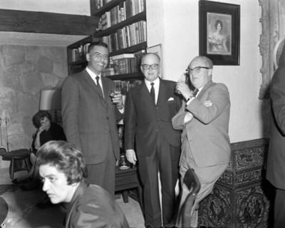 Hombres reunidos sonrien en la sala de una casa, retrato de grupo