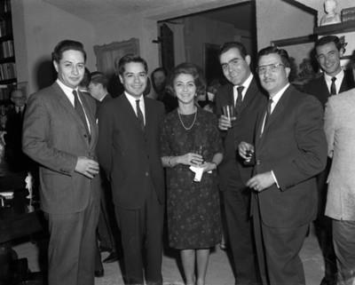 Hombres y mujer con bebidas durante reunión en la sala de una casa, retrato de grupo