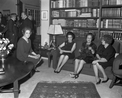 Mujeres sentadas platican en la sala de una casa durante reunión
