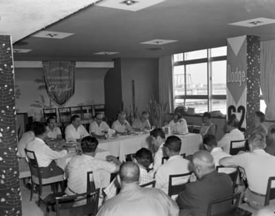 Empresarios en restaurante durante convención de distribuidores de productos Chrysler