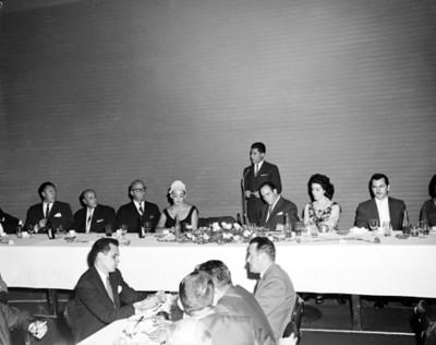 Hombre pronuncia discurso durante banquete en salón de hotel Balsa