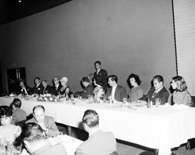 Hombre da discurso durante banquete en salón de hotel Balsa