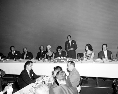 Hombre lee documento ante micrófono durante banquete en salón de hotel Balsa