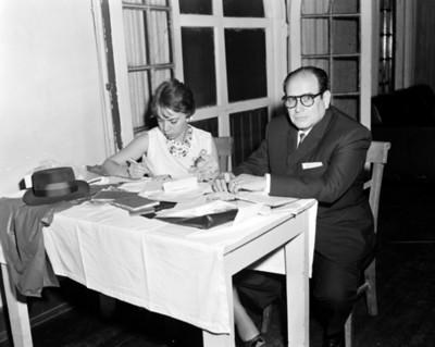Pareja firma documentos en escritorio durante convención de distribuidores Cheysler