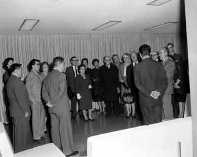 Hombres y mujeres de pie reunidos en uns sala