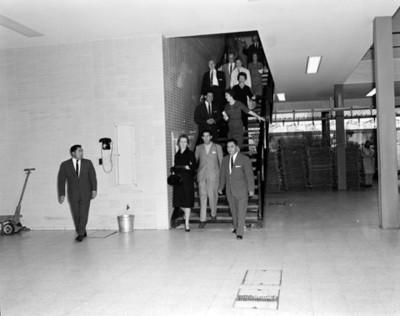 Eva Sámano de López Mateos baja por escaleras de un edificio acompañada por personas