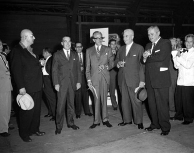 Hombres con bebida en mano durante la inauguración de la Escuela Dina