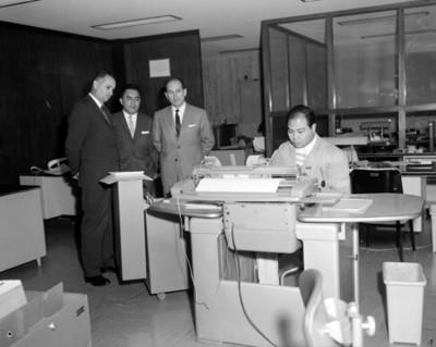 Empleado opera máquina en una oficina es observado por hombres