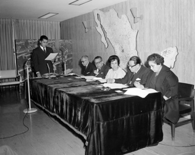 Eva Samano de López Mateos sentada junto a hombres revisan documentos en un salón durante conferencia