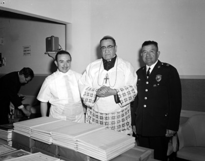 Sacerdote junto a hombres durante la bendición de un consultotio médico, retrato de grupo