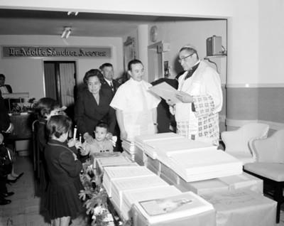 Sacerdote sostiene un cuadro durante la bendición e un consultorio médico