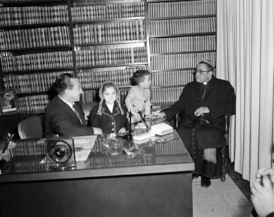 Sacerdote con niños y un hombre durante la bendición de un consultorio