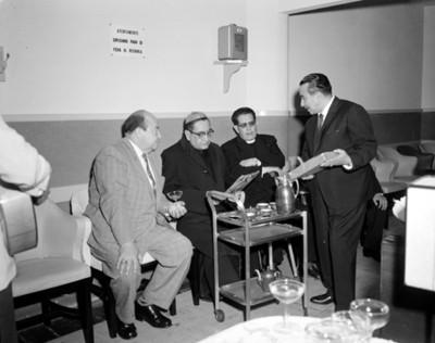 Sacerdote observa imagen religiosa sentado junto a otros hombres durante la bendición de un consultorio médico