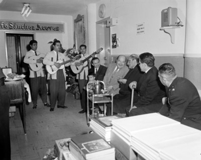 Sacerdote sentado junto a otros hombres escuchan cantar a un trío musical en la sala de espera de un consultorio