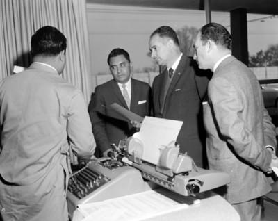 Hombres platican con empleado junto a escritorio con máquina de escribir en una oficina