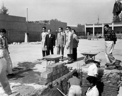 Hombres observan a albañiles durante construcción en escuela