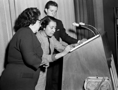 Mujer firma documento en el estrado de un auditorio durante conferencia