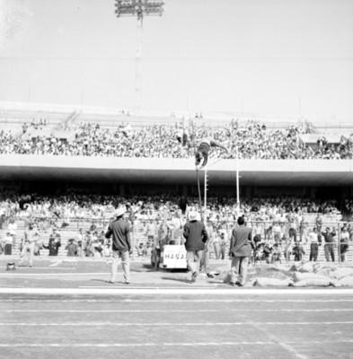 Gente observa a un atleta durante salto de garrocha