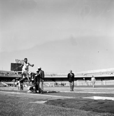 Atleta durante salto de longitud observado por jueces