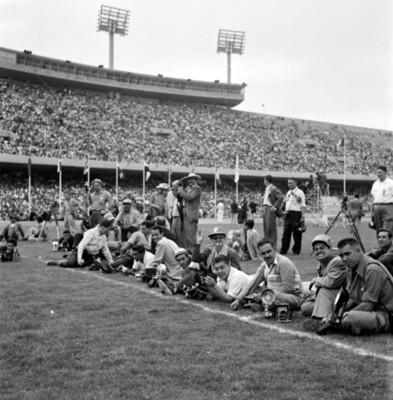 Fotógrafos en cancha de estadio durante celebración de juegos panamericanos