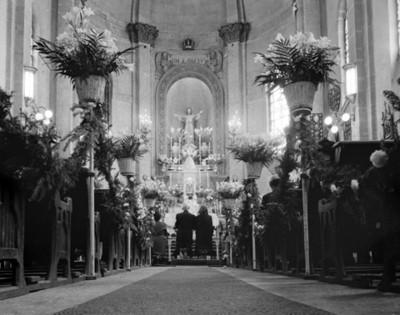 Novios hincados frente a un altar religioso, durante su boda