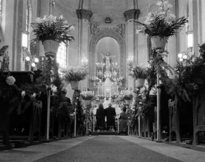 Novios hinchados frente a un altar durante su boda religiosa