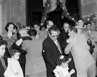 Hombres felicitan a los novios en la entrada de una iglesia después de su boda religiosa