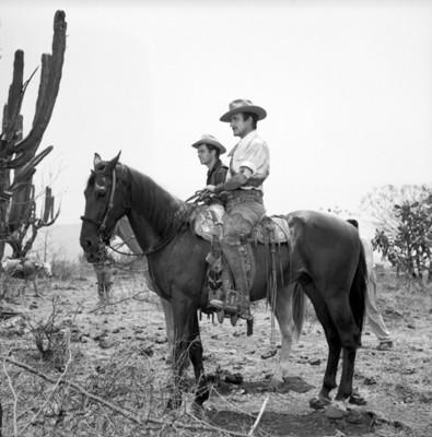 Actores montan caballos durante filmación de película en el campo