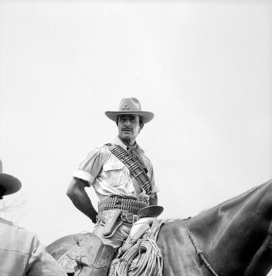Actor monta caballo durante filmación de película, retrato