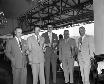 Hombres con trofeos de finalistas en la sala del Hipódromo de las Américas