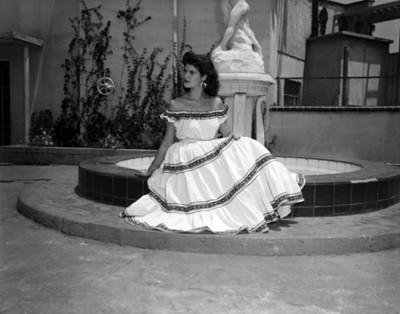 Mujer con traje regional sentada en una fuente, retrato