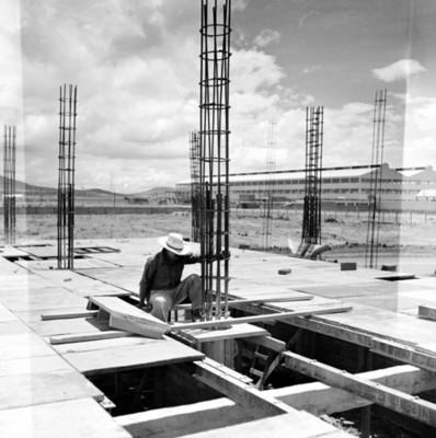 Albañil observa estructuras de acero en azotea durante proceso constructivo