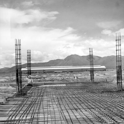 Hombre observa instalación industrial desde estructuras de acero en construcción