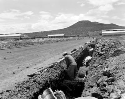 Trabajadores durante excavación a orilla de una carretera, vista parcial