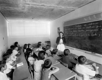 Maestra y alumnos en salón de clases