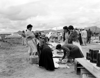 Mujeres observan ropa en un puesto de mercado