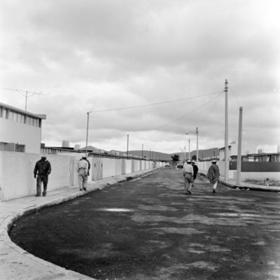 Hombres caminan en una calle de unidad habitacional