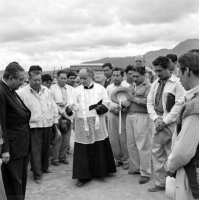 Hombres observan a sacerdote durante bendición en tianguis