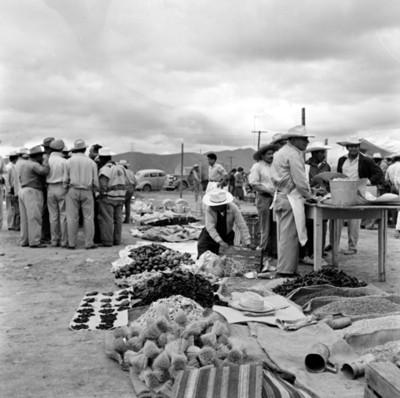 Hombres entre puestos de vendedores ambulantes en tienguis
