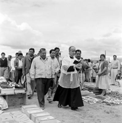 Hombres acompañan a sacerdote durante ceremonia de bendición en tianguis