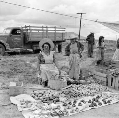 Mujer atiende puesto de frutas y dulces en tianguis, retrato