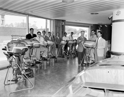 Hombres entre motores de lancha en sala de tienda, retrato de grupo