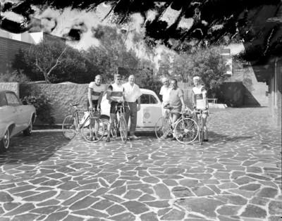 Ciclista frente a automóvil en un patio, retrato de grupo