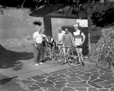 Hombres acompañan a ciclistas en entrada a edificio, retrato de grupo