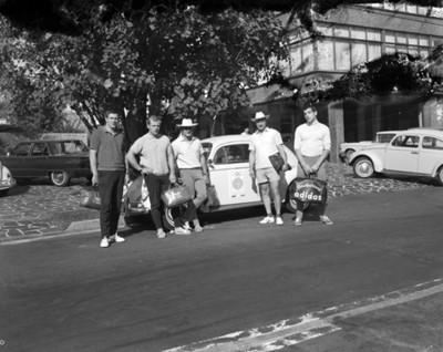 Deportistas junto a automóvil en entrada a edificio, retrato de grupo