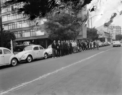 Hombre frente a automóviles volkswagen en entrada a edificio