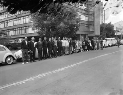 Integrantes de comité olímpico frente a automóviles volkswagen en entrada a edificio, retrato de grupo