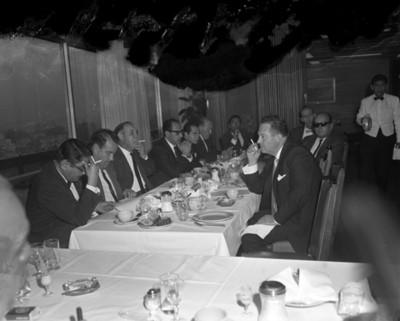 Hombres fuman durante banquete en un salón